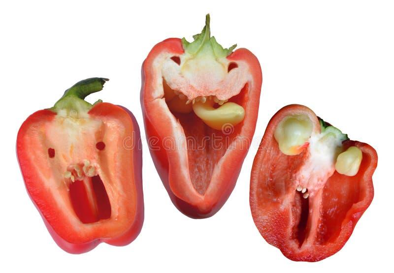 Tre röda roliga peppar som är klara för halloween arkivfoton