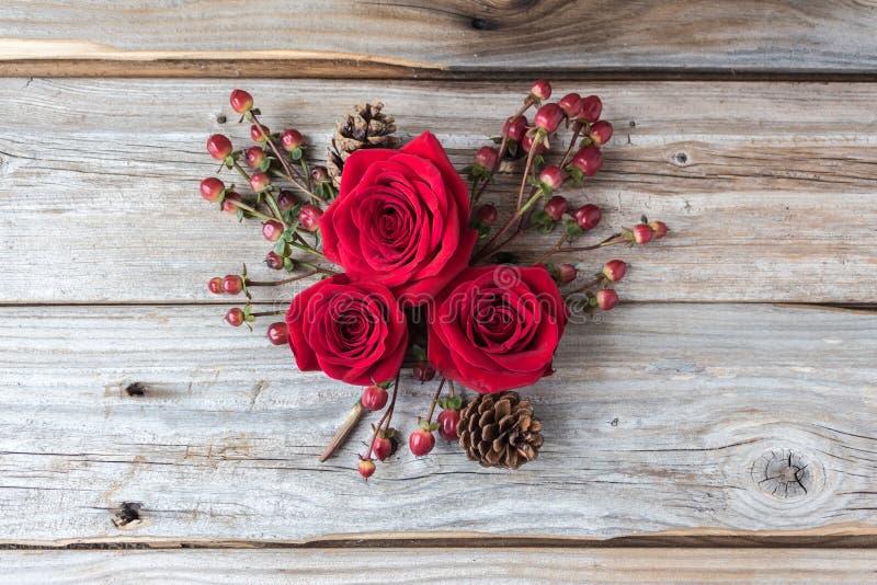 Tre röda rosor i en klunga på lantlig wood bakgrund royaltyfri foto