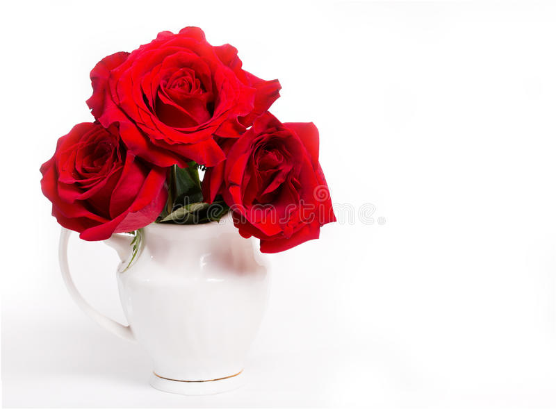 Tre röda rosor i en vit vas på en vit bakgrund arkivfoton