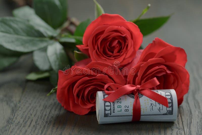 Tre röda rosor och grupp av dollar arkivbild