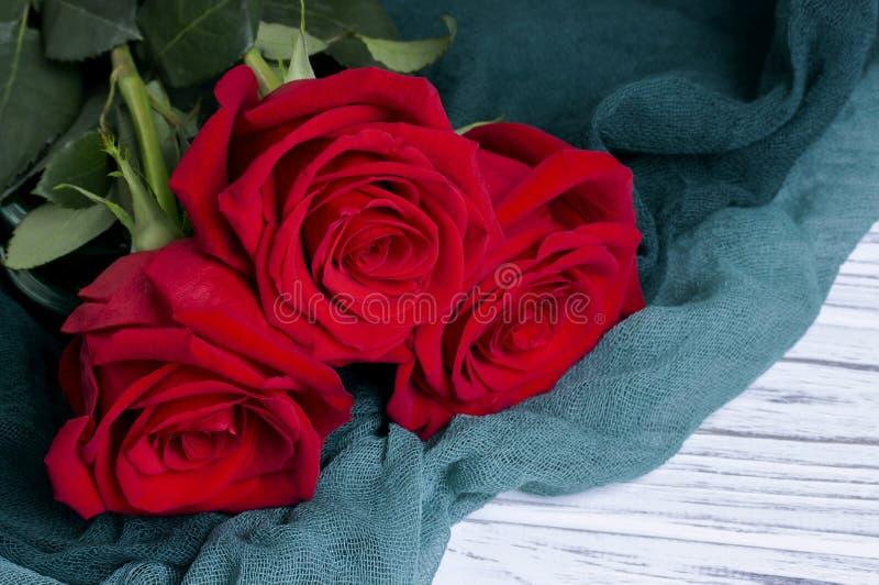 Tre röda rosor på den gröna textilen på vit träbakgrund arkivbild