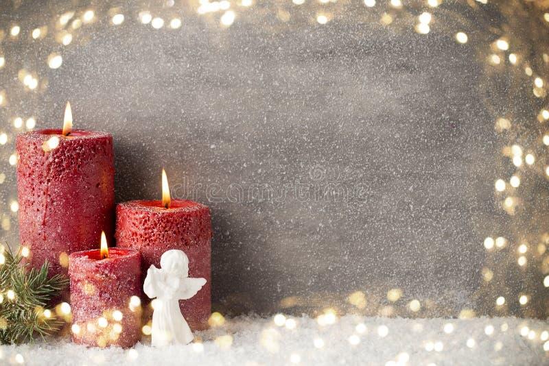 Tre röda stearinljus på grå bakgrund, julgarnering Adve arkivbild