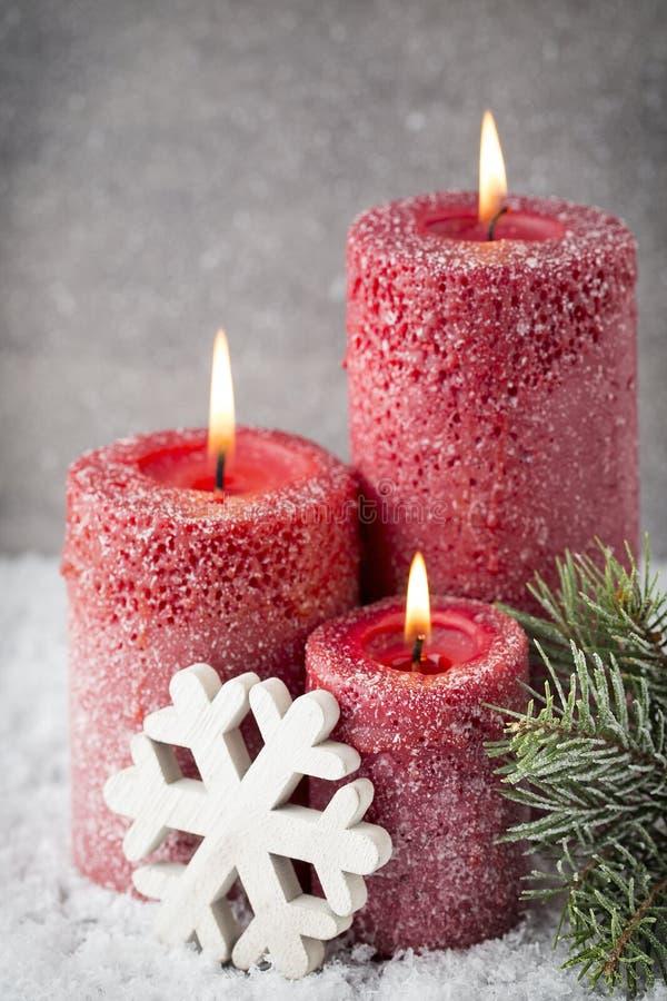 Tre röda stearinljus på grå bakgrund, julgarnering Adve royaltyfria bilder