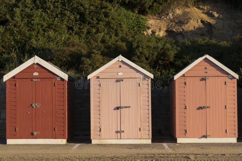 Tre röda strandkojor i olika signaler Dubbla dörrar utan fönster royaltyfri bild