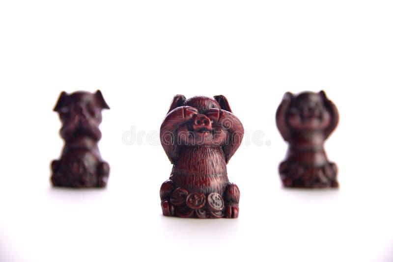 tre röda svin för souvenir på en vit bakgrund royaltyfri foto