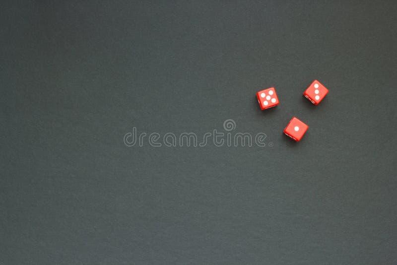 Tre röda tärning på en mörk torkduk, utrymme för text royaltyfria bilder