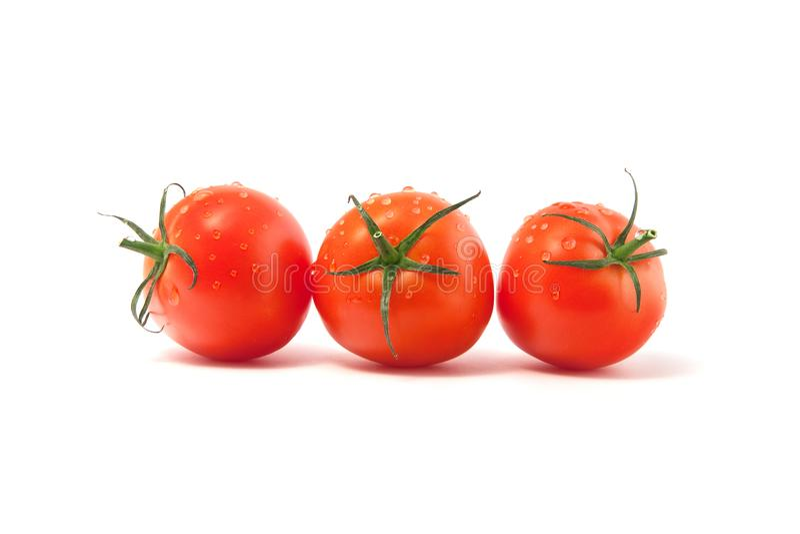 Tre röda tomater som isoleras på en vit bakgrund arkivbild