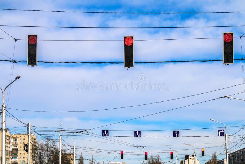 Tre röda trafikljus hänger över vägen mot den blåa himlen Förbudsignal royaltyfria bilder