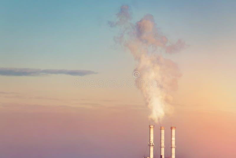 Tre röka buntrör som gör moln av vit rök med dramatisk solnedgånghimmelbakgrund Industriellt minimalistic landskap arkivfoto