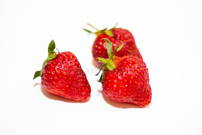Tre r?da jordgubbar med gr?na svansar ligger p? en vit bakgrund, runt om den mjuka skuggan royaltyfria foton