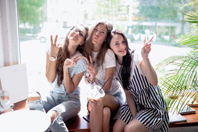 Tre ragazze abbastanza esili con capelli scuri lunghi, stile casuale d'uso, si siedono sul davanzale in una caffetteria moderna fotografia stock