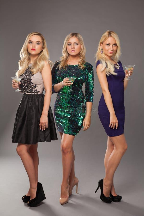 Tre ragazze bionde che portano i vestiti da sera che driknking martini fotografia stock