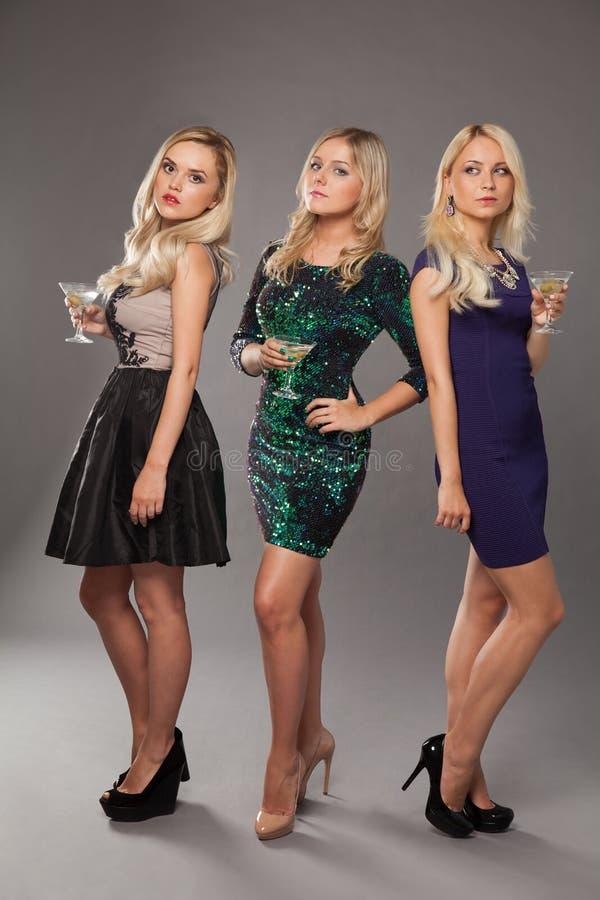 Tre ragazze bionde che portano i vestiti da sera che driknking martini fotografie stock