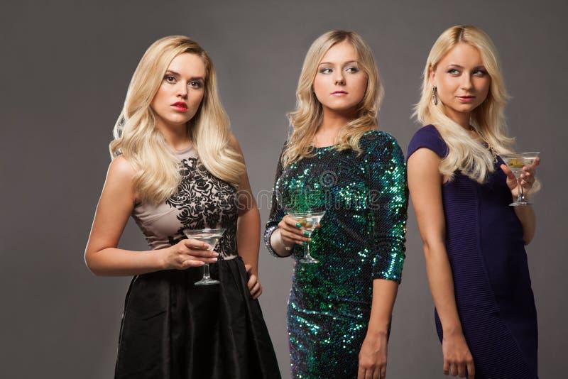 Tre ragazze bionde che portano i vestiti da sera che driknking martini immagini stock