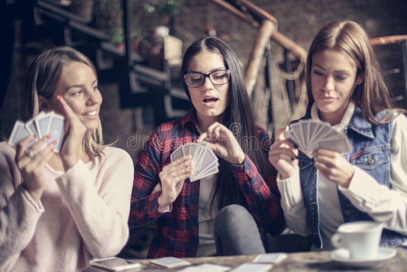 Tre ragazze in caffè che gioca le carte del gioco fotografia stock