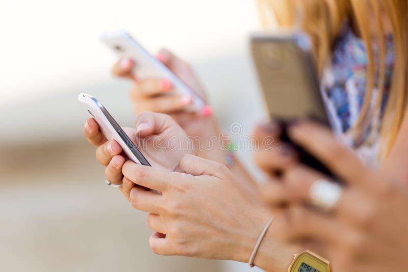 Tre ragazze che chiacchierano con i loro smartphones alla città universitaria immagine stock libera da diritti