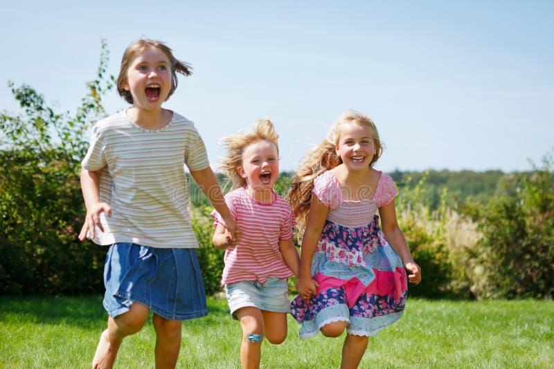 Tre ragazze che eseguono risata esterna fotografia stock