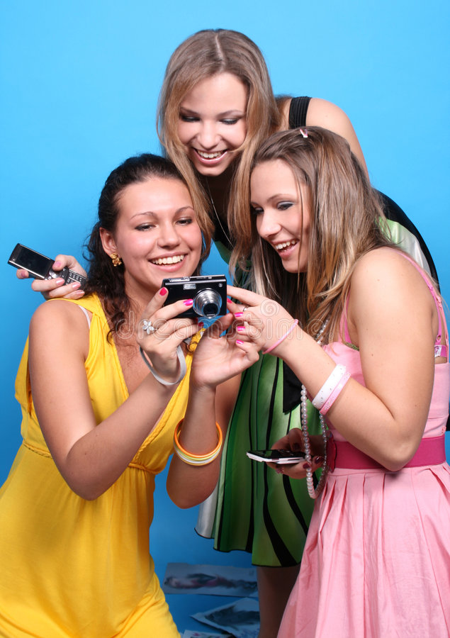 Tre ragazze che hanno divertimento con una macchina fotografica fotografia stock libera da diritti