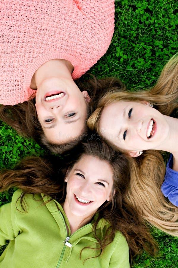 Tre ragazze che si trovano sull'erba fotografia stock libera da diritti