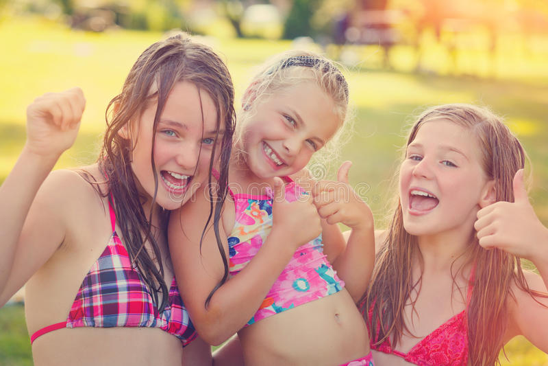 Tre ragazze che sorridono su un prato fotografie stock