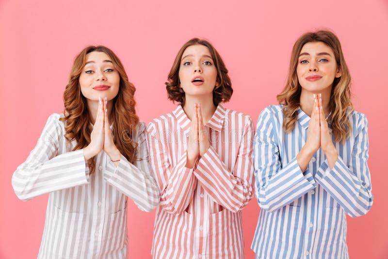 Tre ragazze concentrate 20s che indossano paja a strisce variopinto immagini stock