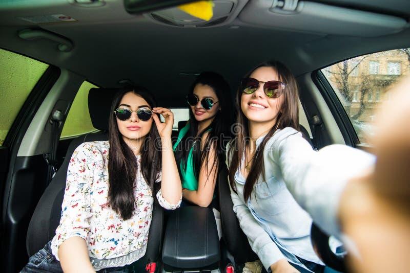 Tre ragazze divertendosi nell'automobile e prendendo i selfies con la macchina fotografica immagini stock