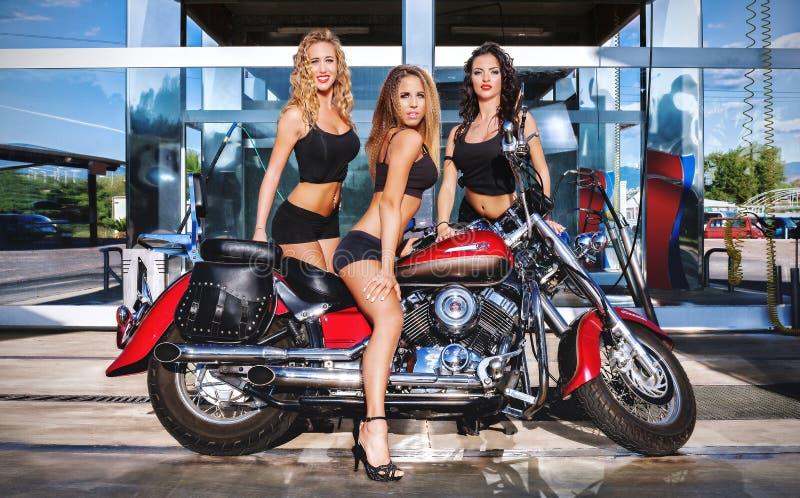 Tre ragazze e un motociclo fotografia stock libera da diritti