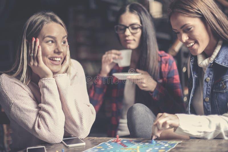 Tre ragazze felici che giocano gioco da tavolo immagini stock