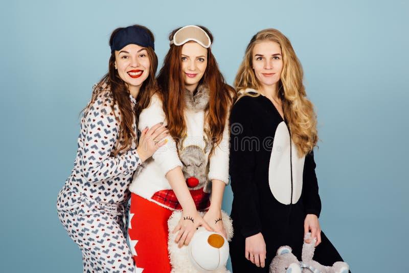 Tre ragazze felici in pigiami tengono i giocattoli in loro mani immagini stock