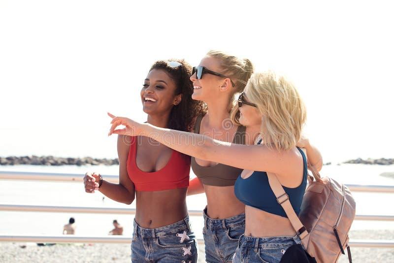Tre ragazze felici sorridenti divertendosi sulla vacanza immagini stock