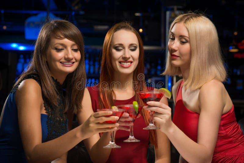 Tre ragazze hanno alzato i loro vetri in un night-club immagini stock