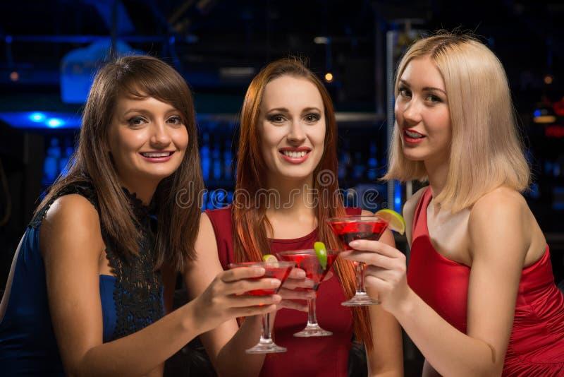 Tre ragazze hanno alzato i loro vetri in un night-club immagini stock libere da diritti