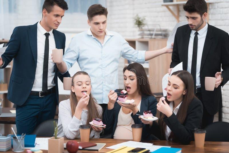 Tre ragazze mangiano il dolce delizioso e non dividono con gli uomini in vestiti fotografie stock