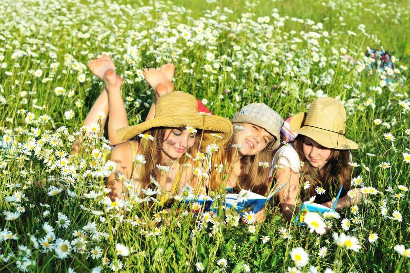 Tre ragazze a piedi nudi leggenti fotografie stock libere da diritti