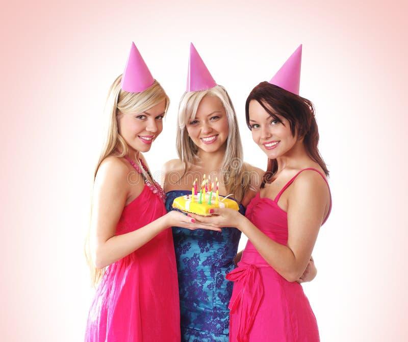 Tre ragazze stanno avendo una festa di compleanno immagini stock
