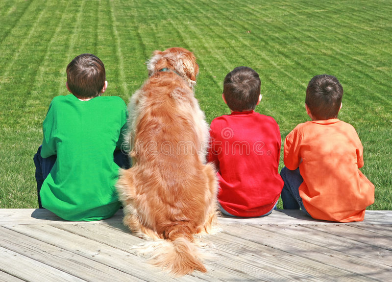 Tre ragazzi e un cane fotografie stock