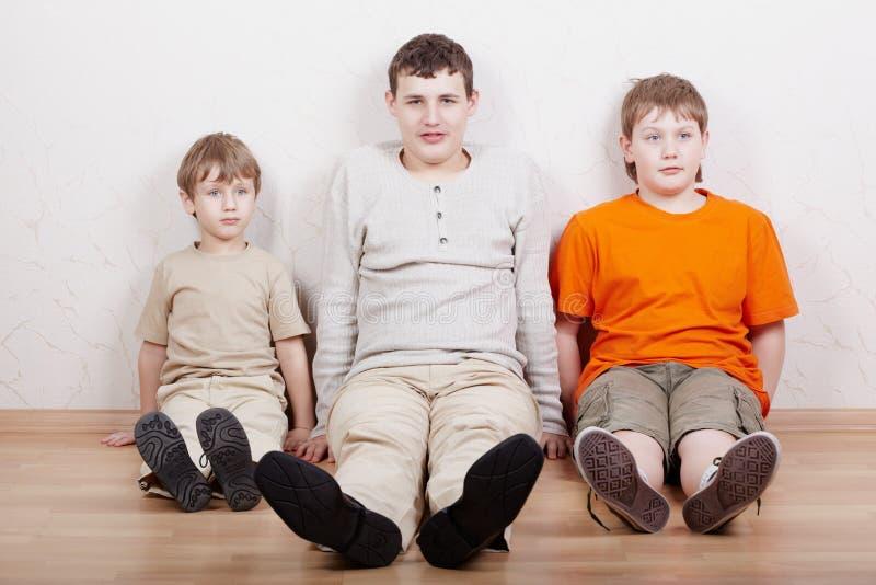 Tre ragazzi si siedono parallelamente sul pavimento fotografie stock