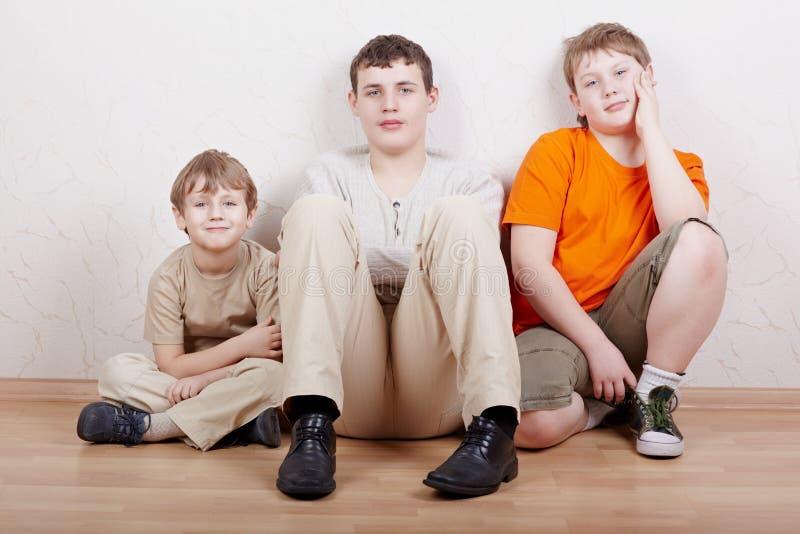 Tre ragazzi si siedono sul pavimento con i loro piedini rimboccati in su fotografia stock libera da diritti