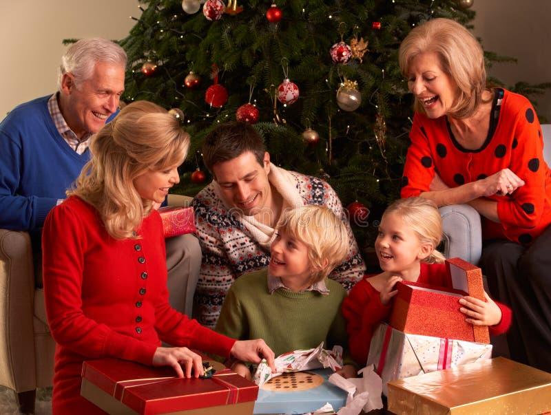 Tre regali di natale di apertura della famiglia della generazione immagini stock libere da diritti
