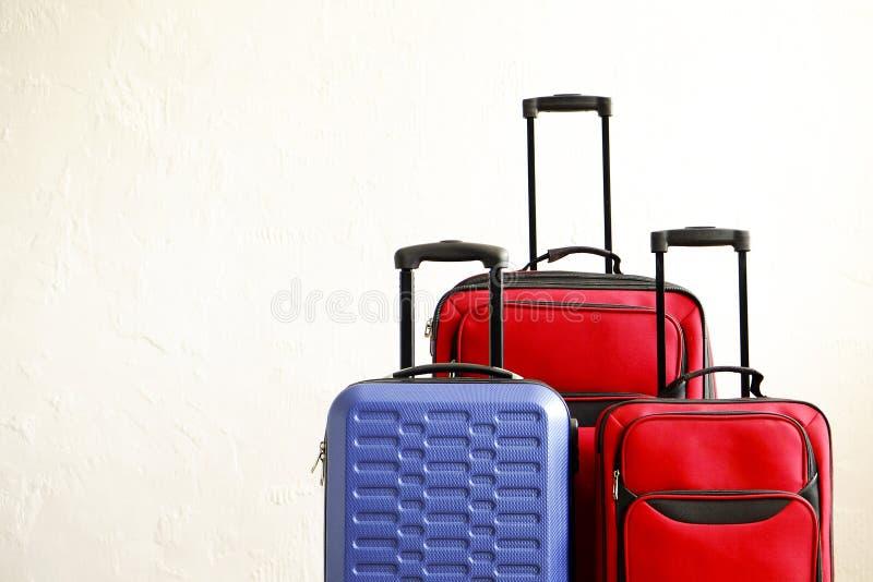 Tre resväskor av olikt format, stor & liten röd textil och blått hårt skalbagage med det fördjupade teleskopiska handtaget Familj arkivbilder