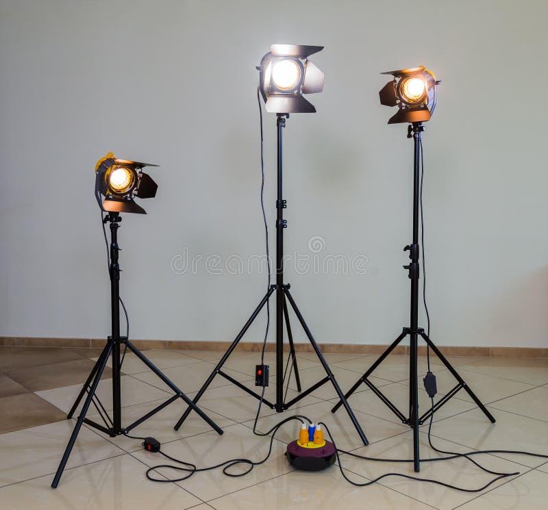 Tre riflettori dell'alogeno con le lenti di Fresnel su un fondo grigio Fotografando e filmare nell'interno immagini stock