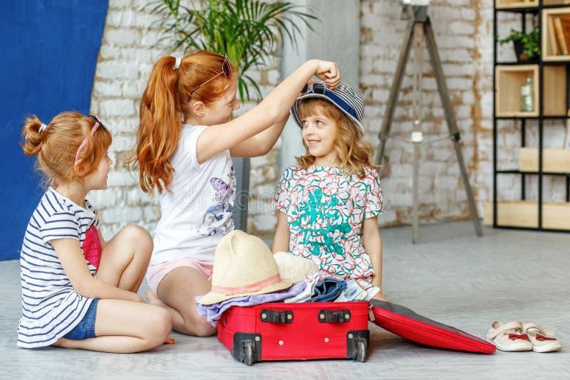 Tre roliga barn av flickor packar en resväska för en strandholida royaltyfria foton