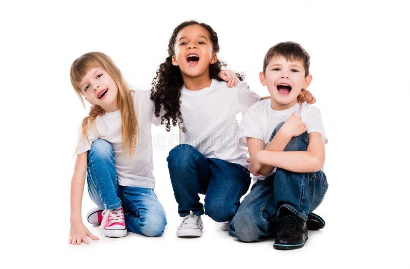 Tre roliga moderiktiga barn skrattar sammanträde på golvet royaltyfria bilder