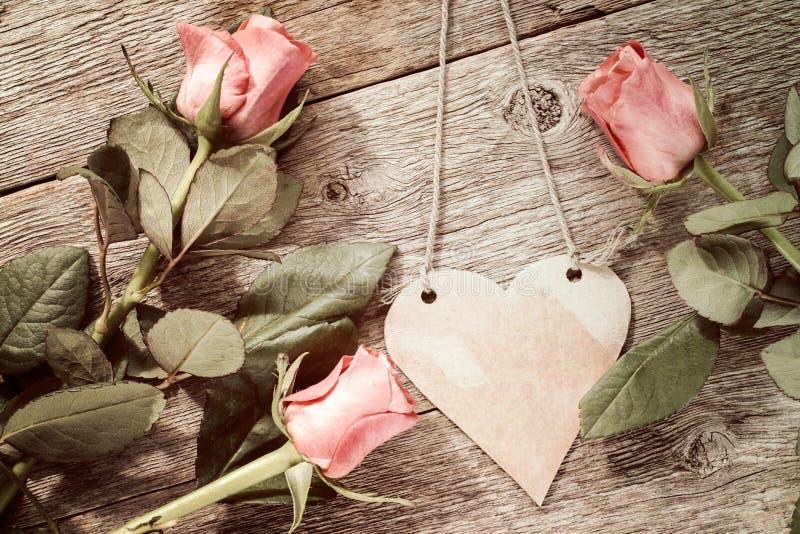 Tre rosor och hängande pappers- hjärta arkivfoto