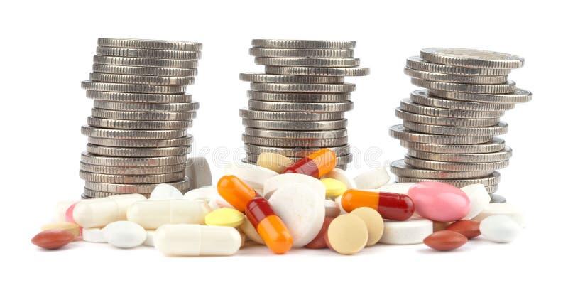 Tre rotoli di euro monete e delle pillole rovesciate immagini stock libere da diritti