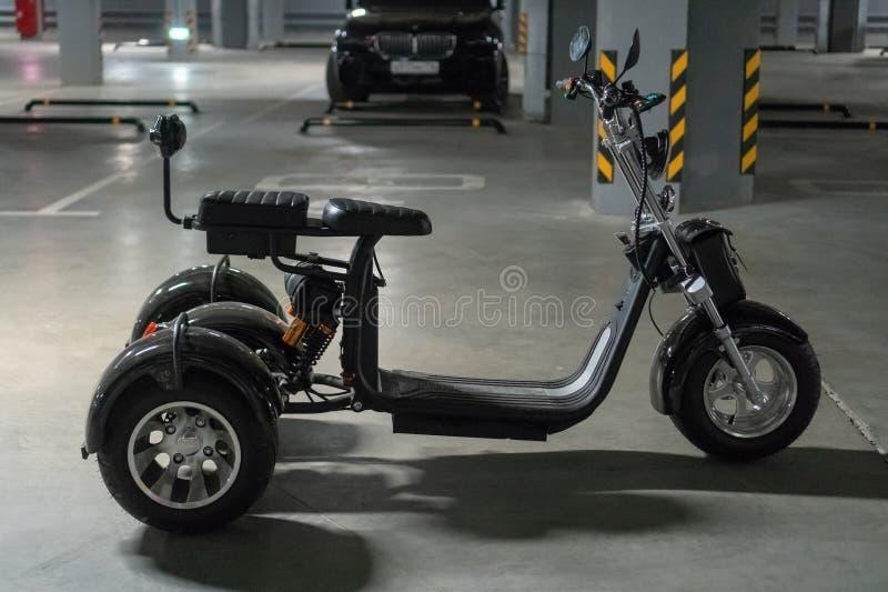 Tre-rullad elektrisk motorcykel på den underjordiska parkeringen arkivfoto