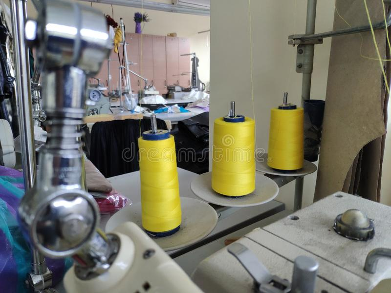 Tre rullar av tråd stoppade in i en symaskin på bakgrunden av en systuga arkivbilder