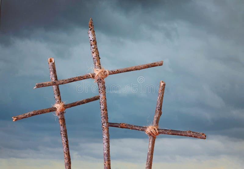 Tre rustici, incroci casalinghi davanti ad un cielo tempestoso che rappresenta la crocifissione di venerdì santo di Jesus Christ  fotografia stock libera da diritti