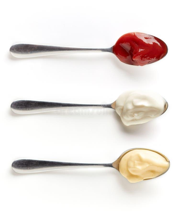 Tre såser i skedar som isoleras på vit, från över royaltyfri foto