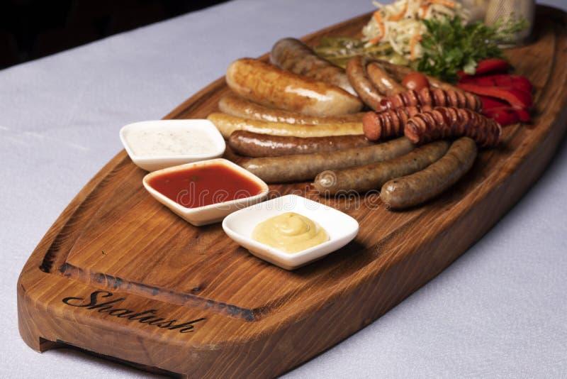 Tre såser med nötköttkorvar, mikrogräsplaner, matleverans royaltyfri foto